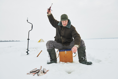 fishing at winter. Fisherman hooking fish on ice