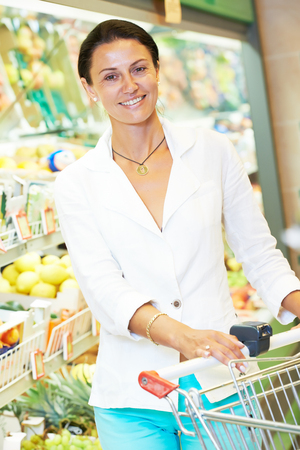 woman with shopping cart in supermarket Stock Photo