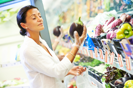 woman choosing eggplant. Vegetable shopping in supermarket