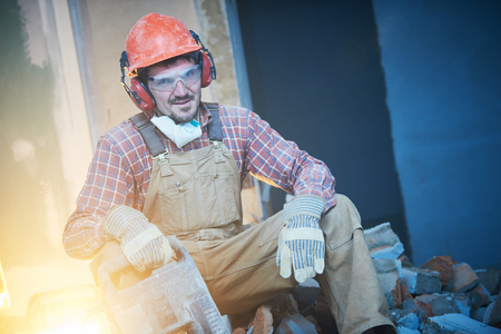 breaking interior wall. worker portrait with demolition hammer
