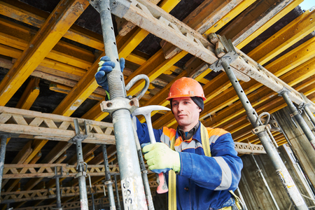 Concrete monolithic building. Builder at installation or dismantling of monolithic formwork. Installing a support pole for formwork construction. Stock Photo