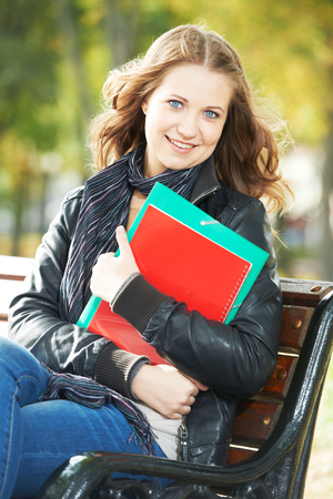 Education and study. happy female student. Girl with note books and workbooks in park outdoors