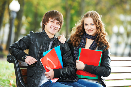 Education and students. Happy young college student with notebooks on bench Stock Photo