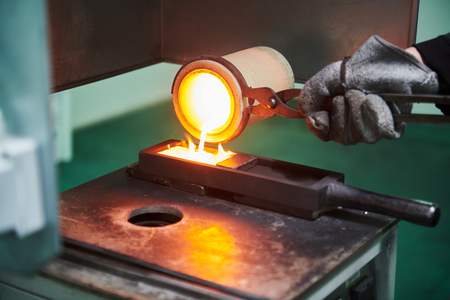 Melting gold. Molted metal pouring into bar form Stock Photo