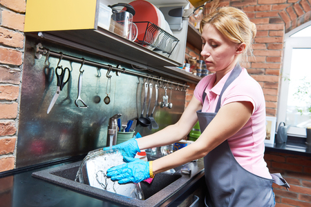 Cleaning service. woman washing dishes at kitchen