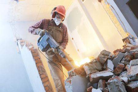 breaking interior wall. worker with demolition hammer