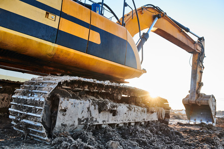 excavation work. Excavator at construction site with sunset