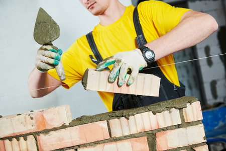 bricklayer builder worker laying bricks wall Reklamní fotografie