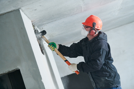 demolition work and rearrangement. worker with sledgehammer destroying wall Reklamní fotografie