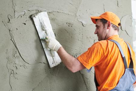 Renovation. Plasterer putting plaster on wall. Stock Photo