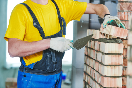 bricklayer builder worker laying bricks wall Stock Photo