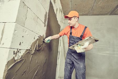 Plasterer applying plaster on block wall. Rennovation