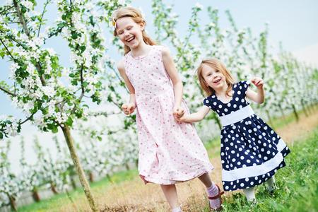 Two little girl run and having fun in spring garden