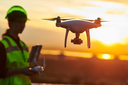 Ispezione con drone. Operatore che ispeziona il cantiere edile volando con il drone. tramonto Archivio Fotografico
