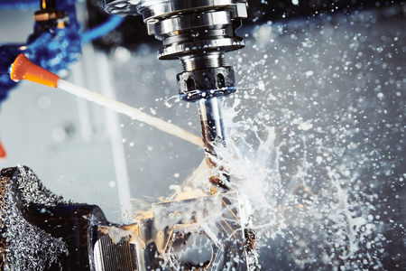 Milling metalworking process. Industrial CNC metal machining by vertical mill. Coolant and lubrication Stock Photo