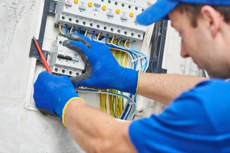 Electrician assembling power switchboard