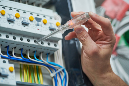 electrician works with electric meter tester in fuse box Stock Photo