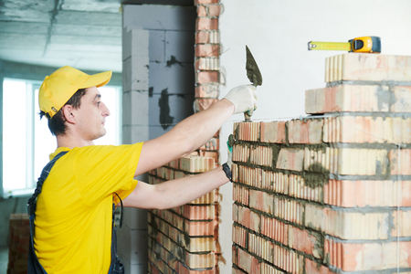 bricklayer builder worker laying bricks wall Stock Photo