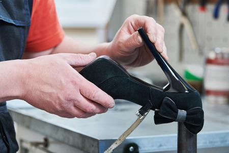 Shoemaker repair female spike shoe. glueing heel Reklamní fotografie