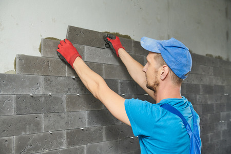 tiler installing ceramic tile panel in hall