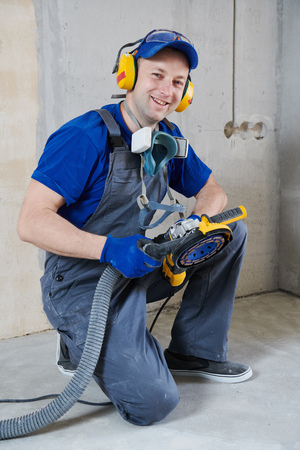 smiling worker at concrete floor surface grinding by angle grinder machine