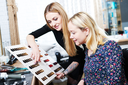 Stylist helps female client to choose hair dye color with hair swatches chart Stock Photo