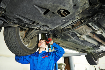 Automobile mechanic inspecting car suspension in service station
