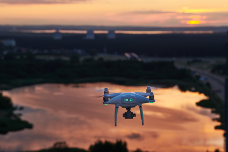 drone quadcopter with digital camera flying at sunset Stock Photo