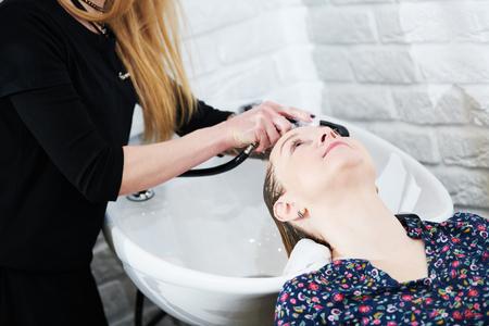 Hairdresser washing female blonde hair. Slow motion