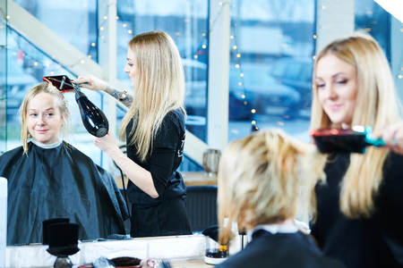 female barber with hairdryer making male haircut. Stock Photo