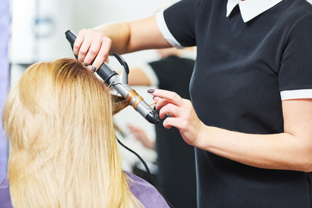 hairdo in beauty salon. hairdresser making coiffure with curl to wonam Stock Photo