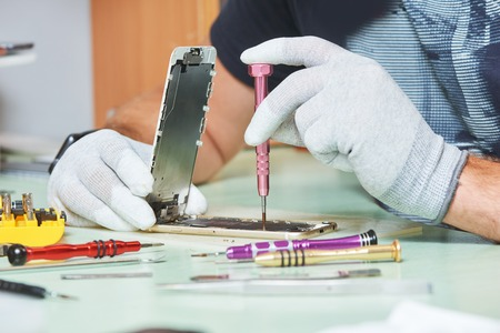 smart phone repair. repairman hands with screwdriver Stock Photo