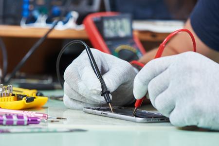 smart phone repair. repairman testing electric circuit Stock Photo