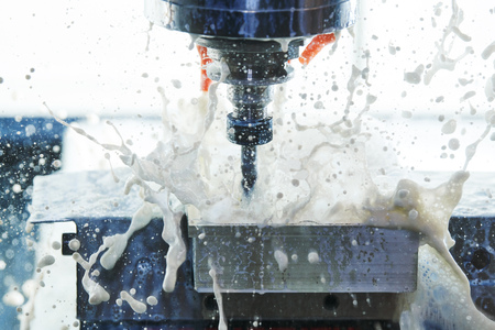 Milling metalworking process. Industrial CNC metal machining by vertical mill. Coolant and lubrication Reklamní fotografie