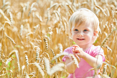 little smiling baby on fields of ripe rye or barley