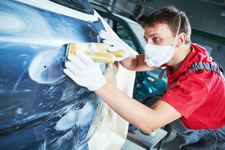 auto repairman grinding automobile body