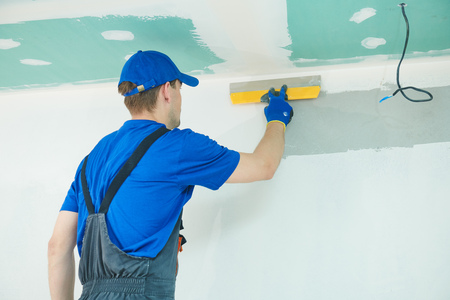 refurbishment. Plasterer worker spackling a wall with putty Stock Photo