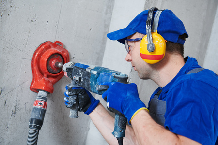 electrician at work. boring hole for electric outlet by power tool drill. Stock Photo