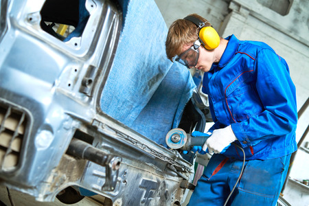 collision repairs service. mechanic grinding car body by grinder Archivio Fotografico