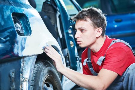 automotive repair. mechanic puttying car body