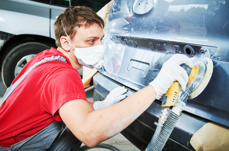 auto repairman grinding autobody Stock Photo