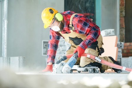 builder at work. cutting concrete floor for cabling by diamond slitting machine