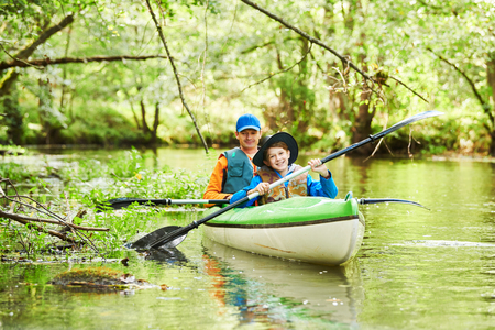 Kayaking on river in forest. Family on canoe. Active recreation and vacation