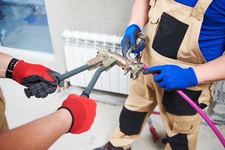 plumber at work. Installing water heating radiator,