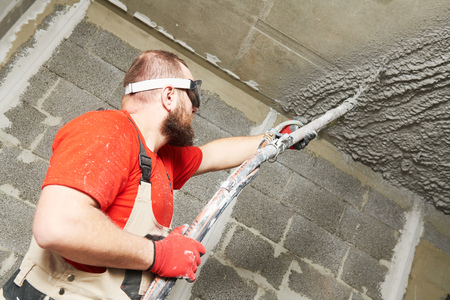 Plasterer using sprayer machine putting plaster mortar on ceiling Standard-Bild - 115229255