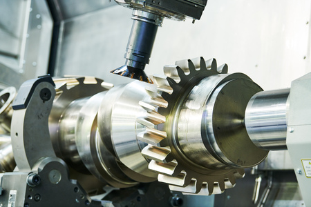 cogwheel on shaft milling process. Industrial CNC metal machining by vertical mill