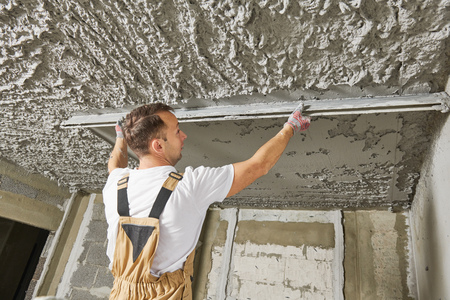 Plasterer smoothing plaster mortar on ceiling with screeder Stockfoto