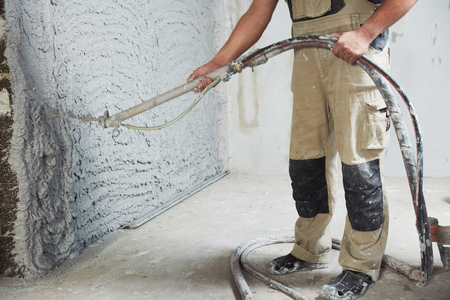plastering the interior wall with an automatic spraying plaster pump machine Stockfoto