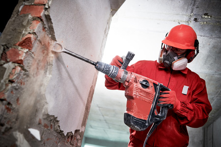 Demolition and construction destroying. worker with hammer breaking interior wall plastering Stockfoto