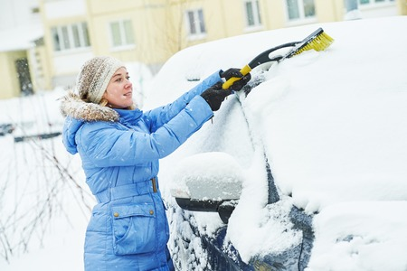 Snow cleaning. Woman cleaning car from snow in winter